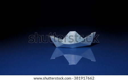 paper boat floating on blue water on black background - stock photo