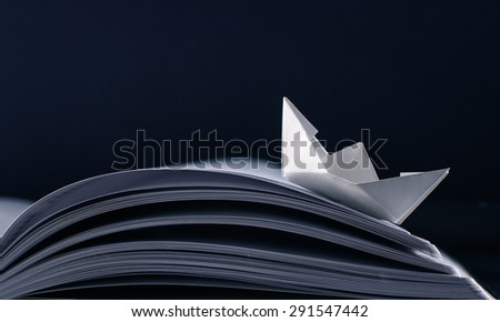Paper boat floating on the pages of a notebook. - stock photo