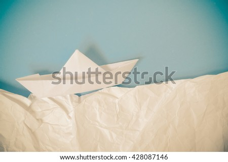 paper boat on blue background - stock photo