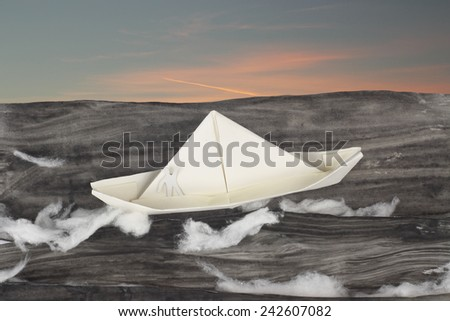 Paper boat sailing in the dangerous  ocean - stock photo