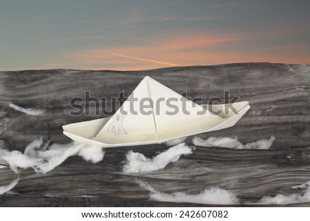 Paper boat sailing in the dangerous  ocean - stock photo