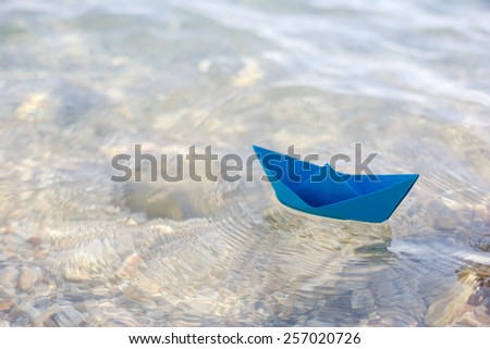 paper boat sailing on water - stock photo