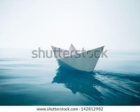 paper boat sailing on water causing waves and ripples - stock photo