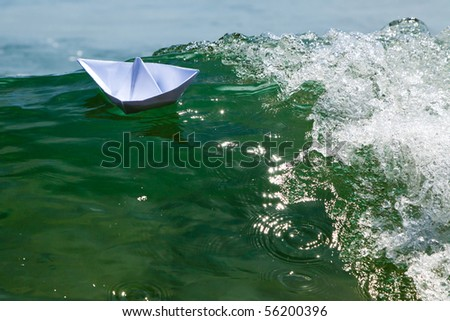 Paper boat struggling with a huge foamy waves - stock photo