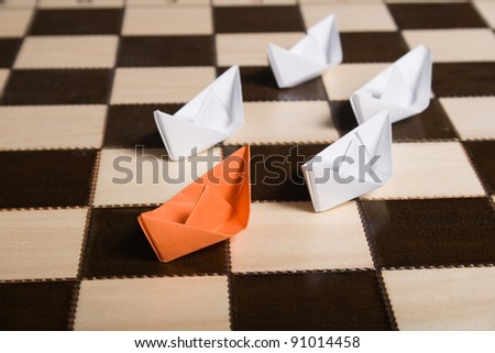 Paper boats on the chessboard. The metaphor of the business. - stock photo