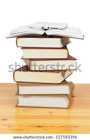 Paper books and ebook on wood table against a white background - stock photo