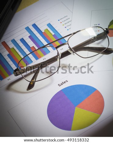 Paper business chart and eyeglasses on the table