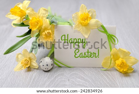 "Paper card ""Happy Easter"", narcissus flowers and quail egg - stock photo"