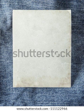 Paper card on blue jeans fabric - stock photo
