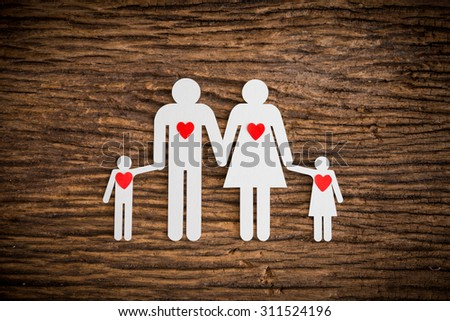 paper chain family and red heart symbolizing on wooden background. love family concept