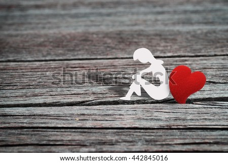 Paper character of woman sitting alone with one heart shape ,grunge wood background. Abstract love background in lonely love or broken heart concept for Valentine's day season. Vintage style. - stock photo