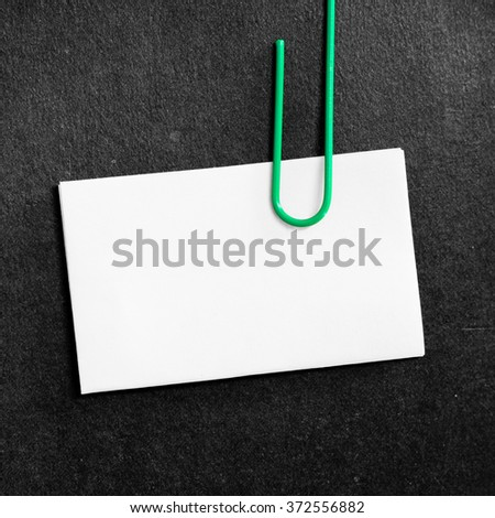 Paper clip clipping white paper on black background - stock photo