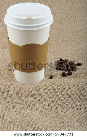 Paper coffee cup with safety cardboard collar on jute background with a big copy space in front - stock photo