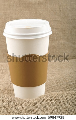 Paper coffee cup with safety cardboard collar on jute background with a copy space.