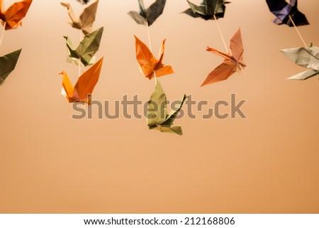 Paper Cranes on Orange Background - stock photo