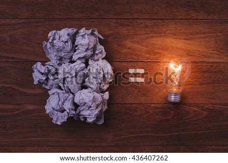 Paper crumpled and Light bulb on wooden background. Concept fot idea. Concept for success. Concept for brainstorming. Concept for solution. Concept for business. - stock photo