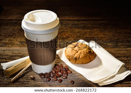 Paper cup of coffee and cookie on wooden background - stock photo
