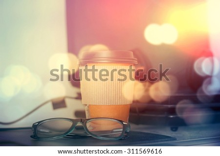 Paper cup of coffee and laptop - stock photo