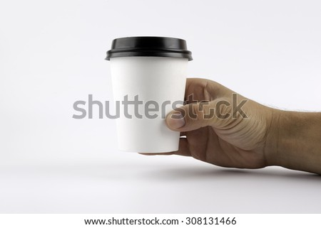 Paper cup of coffee in hand - stock photo