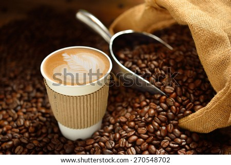 Paper cup of coffee latte and coffee beans on wooden table - stock photo