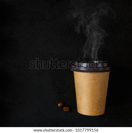 Paper cup of coffee little bit coffee beans and coffee steam on black background. Place for text or price.