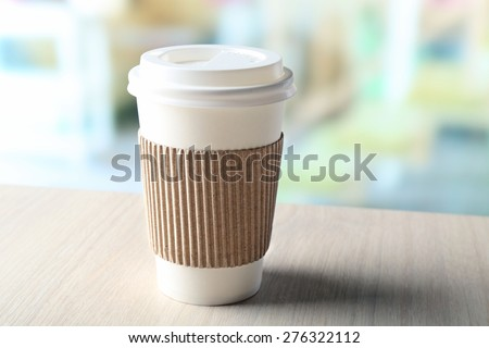 Paper cup of coffee on table on bright background - stock photo