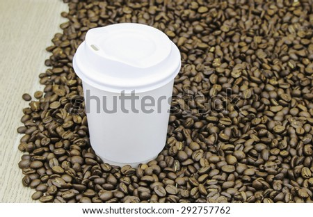 Paper cup of coffee with beans close up - stock photo