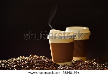 Paper cup of coffee with smoke and coffee beans - stock photo