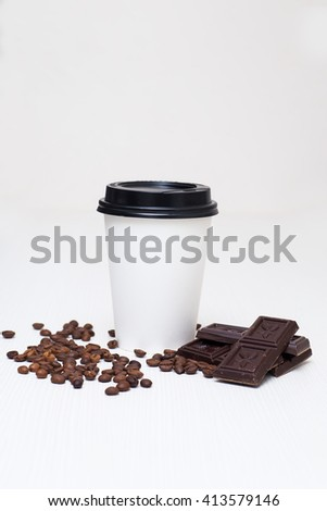 paper cup with coffee and pieces of chocolate on white background