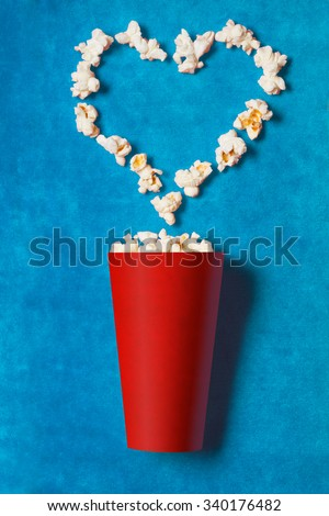 paper cup with popcorn on blue background. mock up. top view. - stock photo