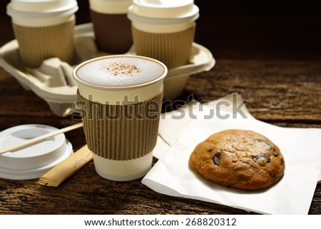 Paper cups of coffee and cookie on wooden background - stock photo