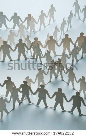 Paper cut figures connected to one another - stock photo
