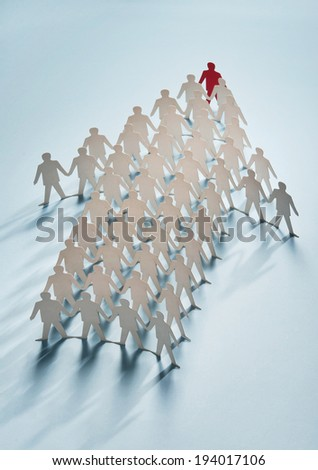 Paper cut figures standing in form of an arrow - stock photo