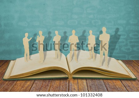 Paper cut of  business man  on old book