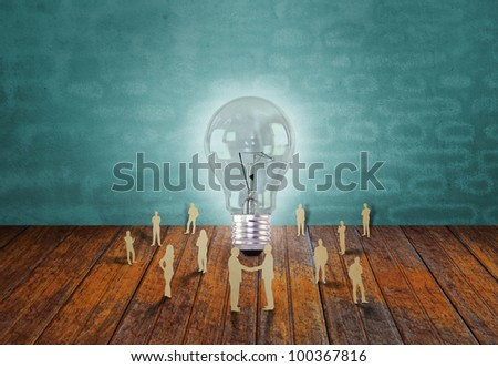 Paper cut of business people and light bulb - stock photo