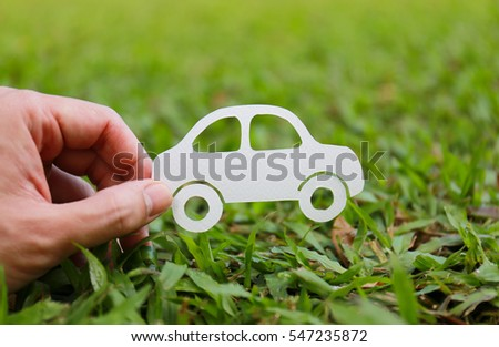 Paper cut of car on green grass background, earth day concept, spring time