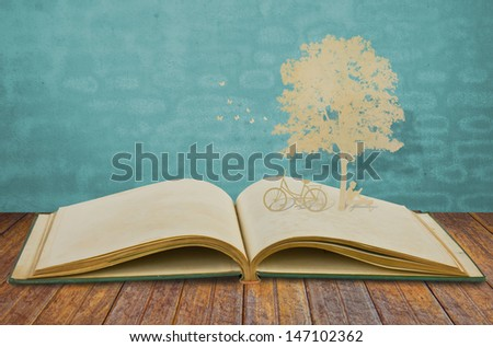 Paper cut of children read a book under tree on old book