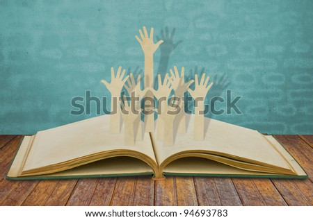 Paper cut of Hands volunteering or voting on old book - stock photo