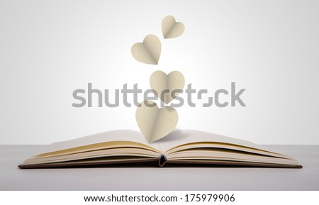 Paper cut of heart on old book - stock photo