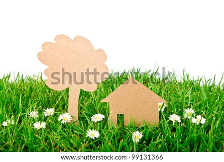Paper cut of house and tree on  fresh spring green grass - stock photo