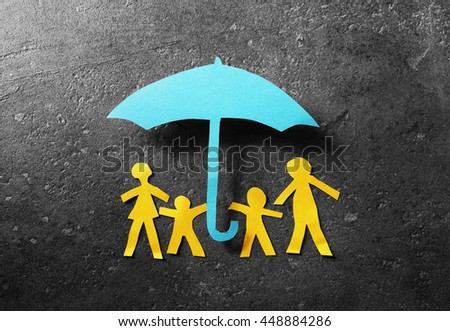 Paper cutout family of four under a blue paper umbrella