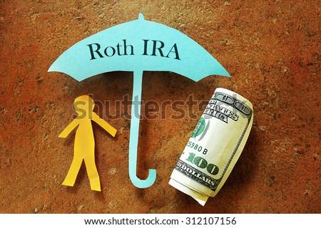 Paper cutout person under a Roth IRA umbrella                                - stock photo
