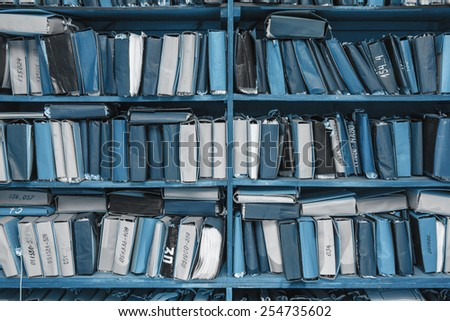 Paper documents stacked in archive on shelf - stock photo