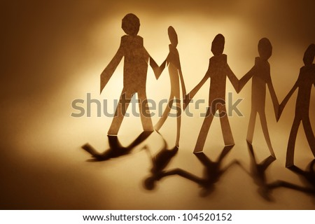 Paper doll cutouts holding hands - stock photo