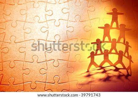 Paper doll team holding hands and jigsaw puzzle. - stock photo