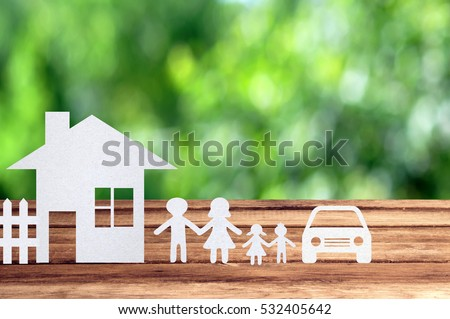 Paper family, house and car on wooden table with garden bokeh outdoor theme background