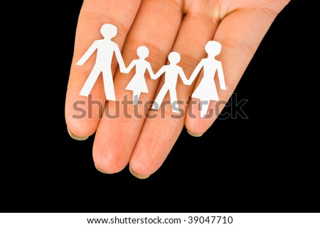 Paper family in hand isolated on black background