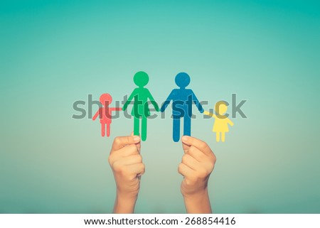 Paper family in hands against summer sky background