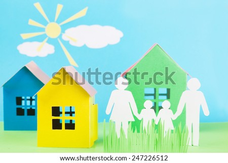 paper family is holding hands beside their new paper house - stock photo