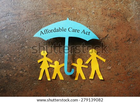 Paper family of four under a Affordable Care Act umbrella                                - stock photo